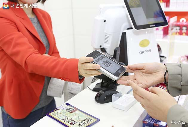 명동에 위치한 한 가게에서 중국 관광객이 알리페이(중국의 간편결제 서비스)를 이용해 물품 대금을 지급하고 있다