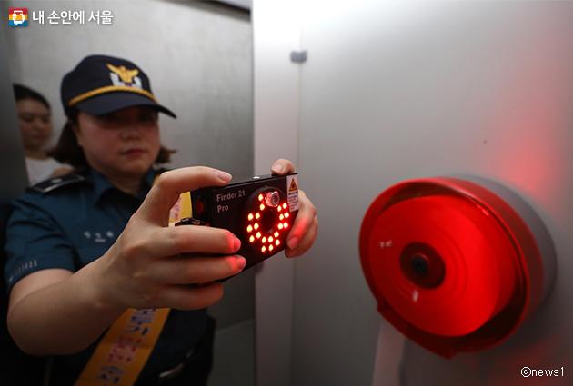 여성안심보안관이 공공화장실에 몰래카메라가 설치되어 있진 않은지 점검 중이다