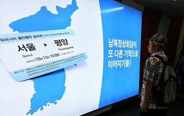 한 시민이 '남북정상회담이 또 다른 기적으로 이어지기를!'이라 써 있는 지하철 포스터를 보고 있다