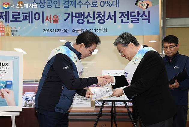 박원순 시장이 정인대 서울소상공인 명예시장으로부터 제로페이 가맹점 신청서를 전달받고 있다