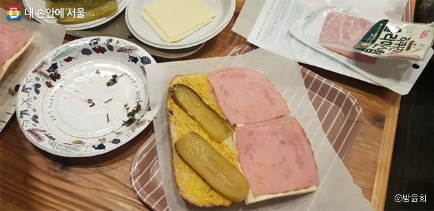 빵 위에 햄, 모조포크, 스위스 치즈 슬라이스, 피클 슬라이스를 얹고서 나머지 쿠바빵을 덮는다.