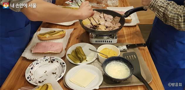 쿠바 샌드위치에 들어갈 햄과 모조포크를 팬 위에서 살짝 굽는다.