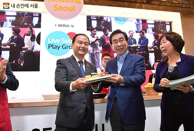 서울 쿠킹쇼에서 북경시 여유국장에게 공화문-천안문 타르트를 전달하고 있는 박원순 시장