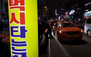 한 계도요원이 택시승차대 앞에서 승객없이 지나가는 택시를 세우고 승차거부여부를 확인하고 있다