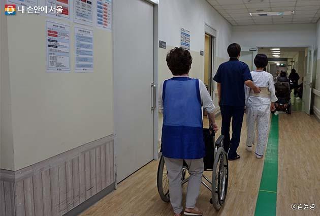 재활의학센터 바닥에 그려져 있는 초록색 선을 따라 운동하는 환자들