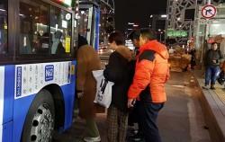 버스 정류소에서 승객들이 올빼미버스에 승차하고 있다