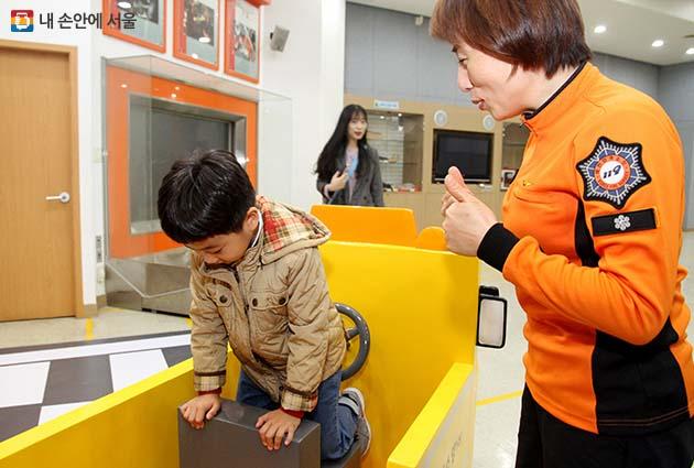 한 아이가 양천구 소방서 체험장에서 차량에 갇혔을 때 대처방법을 배우고 있다.