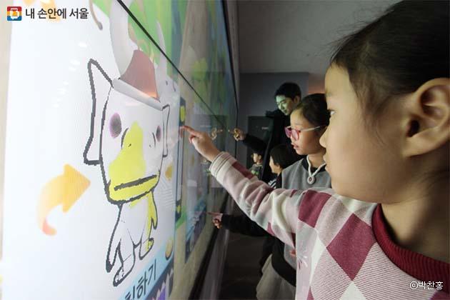 디지털 스케치북 등의 다양한 메뉴로 체험중인 어린이와 부모들의 모습