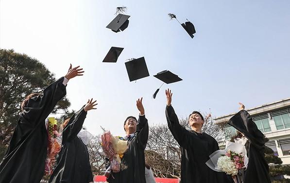 학위수여식에서 졸업생들이 학사모를 던지며 졸업을 축하하고 있다.