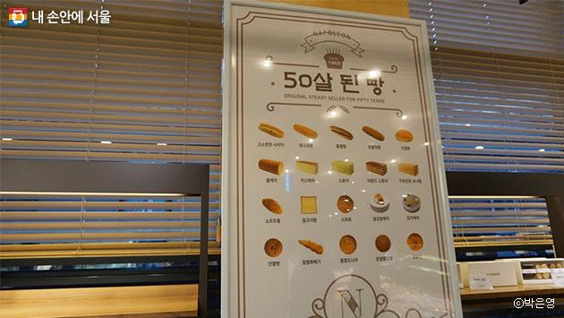 50년 된 빵의 목록을 보여주는 매장 내 포스터