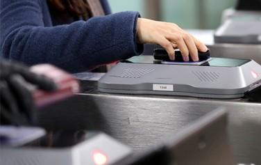 지하철 출구에서 교통카드를 찍고 있는 시민