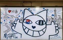 합정역 5번 출구 광고판에 그려진 '무슈샤 웃는 고양이' 그래피티
