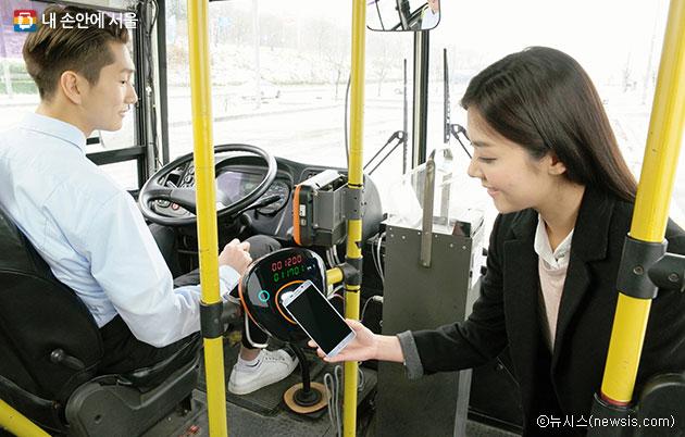 버스 이용자가 버스 교통카드 단말기에 태그하고 있다.