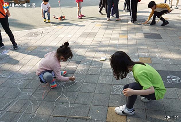 바닥에 그림을 그리는 어린이들