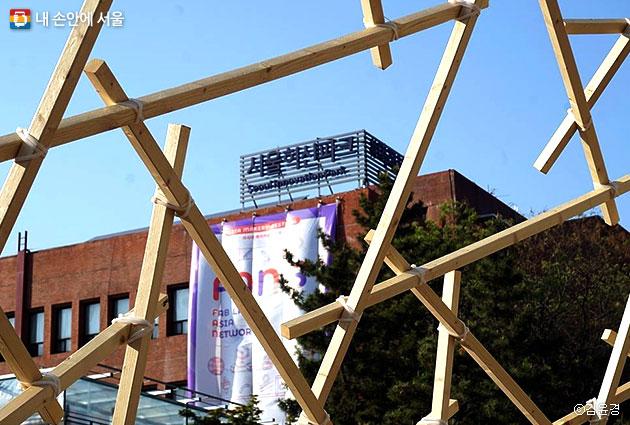나무를 만든 반구형 공간 사이로 서울혁신파크 빌딩이 보인다