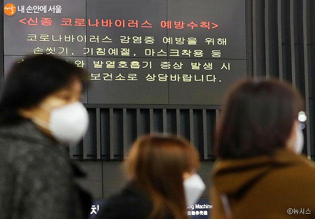 강남구 수서역 대합실에서 마스크를 쓴 시민들이 우한 폐렴 관련 안내 전광판 앞을 지나가고 있다.