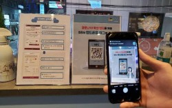 한 입장객이 휴대폰으로 QR코드 스캔후 출입등록절차를 진행하고 있다.
