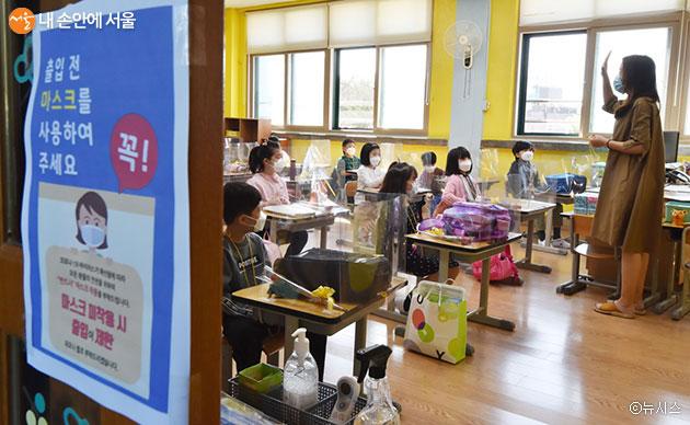 등교가 시작된 27일 초등학교 1학년 신입생들이 선생님으로부터 유의사항을 듣고 있다
