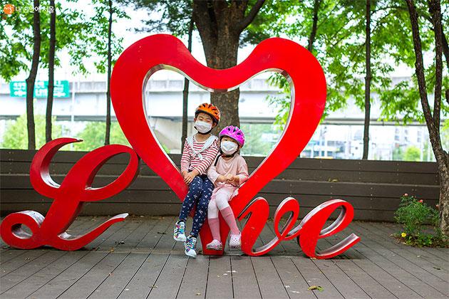 Love 포토존에서 자매가 함께 사진을 찍고 있다