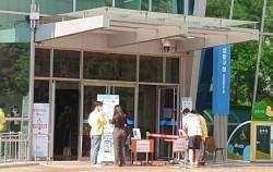 성동구청 출입문 앞에서 사람들이 모바일 전자명부를 작성하고 있다.