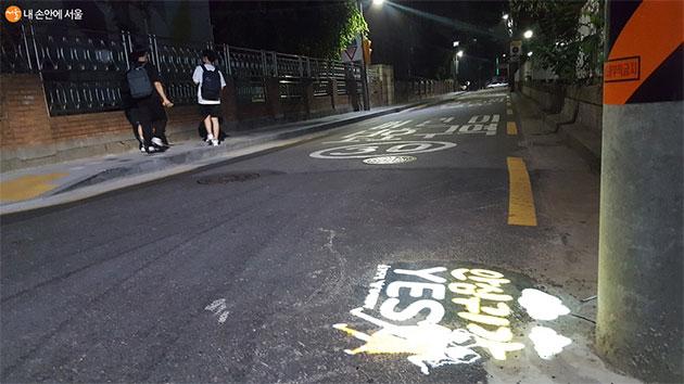 어두운 밤 로고젝터가 설치된 골목길을 학생들이 지나고 있다.