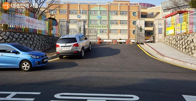 초등학교 정문에 황색 복선을 통해 주정차 금지를 알린다.