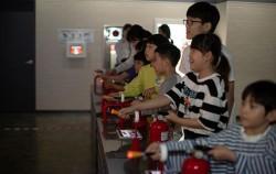 아이들이 목동재난체험관 2층 소화기 시뮬레이터를 이용해 불을 끄는 체험을 하고있다