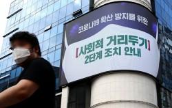 서울 중구 명동거리에서 한 시민이 전광판에 나오는 마스크 쓰기 캠페인 화면 앞을 지나고 있다.