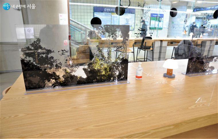 'LOUNGE 사이' 테이블에 설치된 코로나19 예방용 아크릴 가림막은 중간에 자연 풍경을 넣어 안정감을 도모하였다 ⓒ조수봉