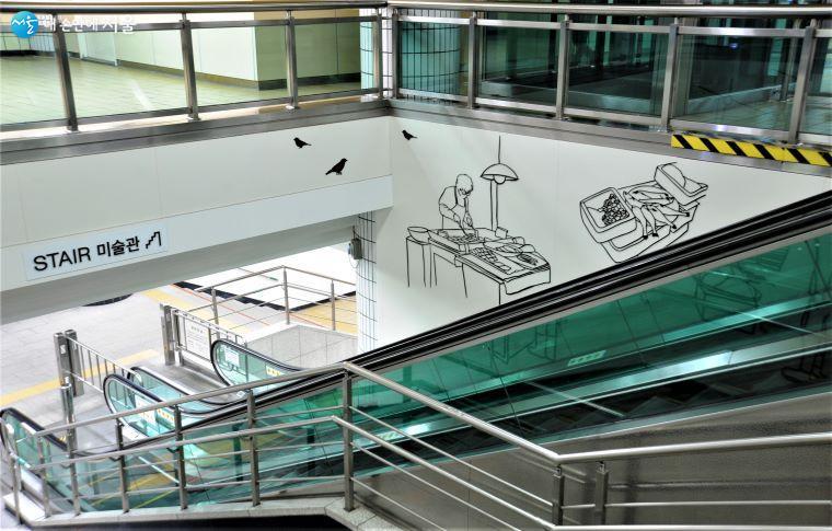 지하 1·2층을 연결하는 에스컬레이터 공간에 설치한 'STAIR 미술관'에는 작가 황혜선의 「시장 풍경」 세 작품이 전시되었다  ⓒ조수봉