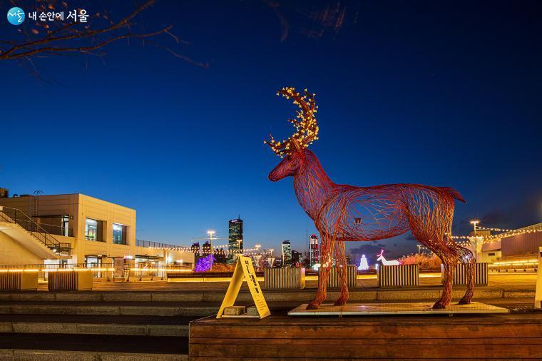 매직아워(Masic Hour; 일몰 후 수십 분 정도로 색상이 부드럽고 따뜻한 상태가 되는 시간)로 파랗게 변한 하늘을 배경으로 보색이라 더욱 대비되는 붉은 사슴이 노란 장식을 하고 노들섬에 나타났다 ⓒ양인억