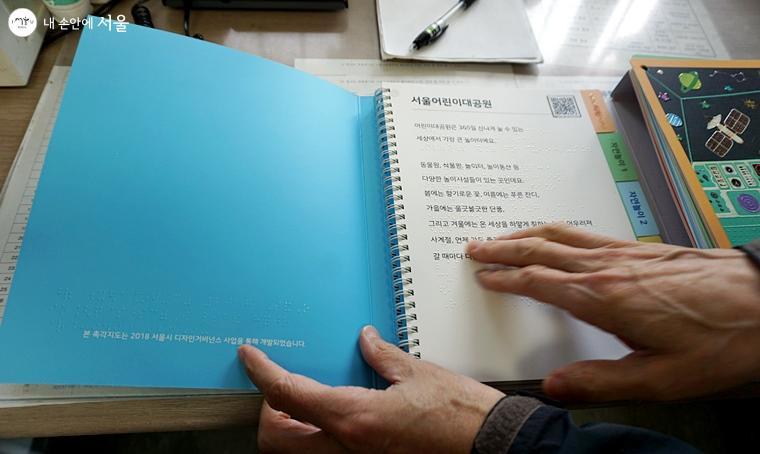 담당자가 책의 점자를 설명하고 있다.