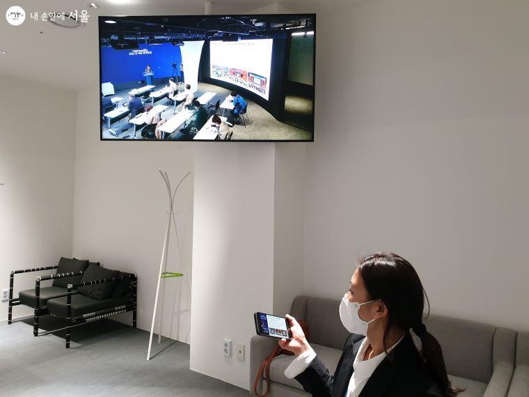 행사 담당자가 행사장과 유튜브를 번갈아보면서 진행 상황을 점검하고 있다.