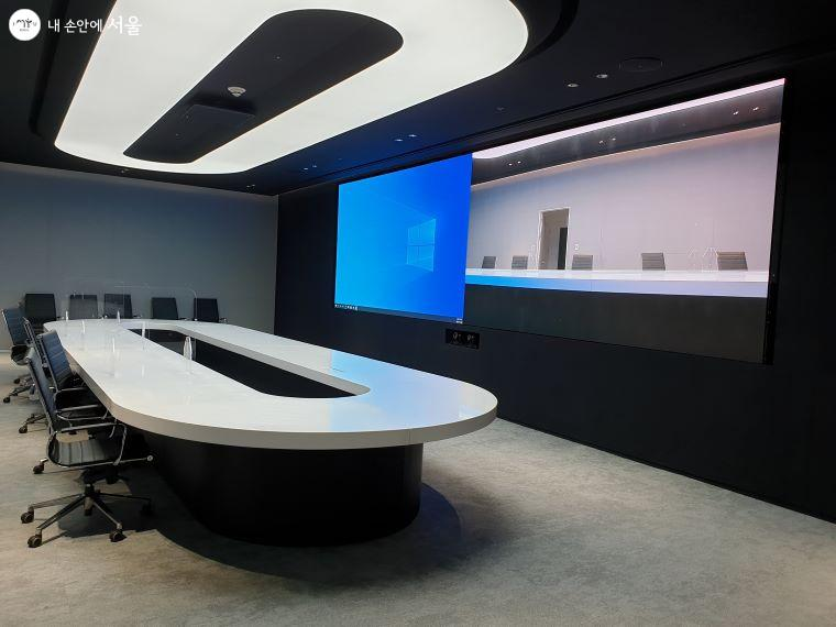 화상 회의실에도 벽면에 대형 디스플레이가 설치되어 있다.