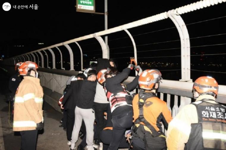 지난 5월 1일 마포대교 난간에서 20대 남성이 투신하려는 것을 경찰관과 고등학생들이 붙잡고 구조하는 중이다.