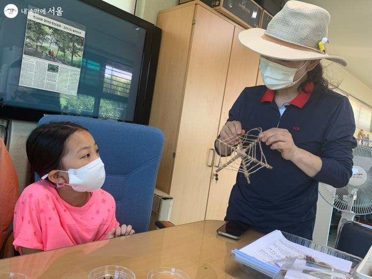 키트를 나눠주고 거미줄 만들기 시범을 보여주고 있다.