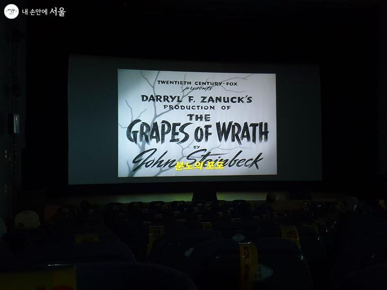스크린에 영화의 시작을 알리는 제목이 자막으로 나오고 있다.